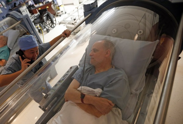 Dr. Andy Chiou speaks to patient Carl Dolson in a hyperbaric chamber in Peoria, Ill., on Nov. 26, 2013. Patients and doctors across the country are piloting Accountable Care Organizations, a health reform under Obamacare.