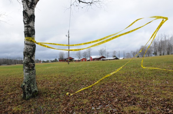 Crime scene tape flies in the wind at the Piscataquis Valley Fairgrounds on Wednesday, Nov. 30, 2011. Michael Curtis was gunned down by police at this location after shooting and killing Udo Schneider only moments earlier.