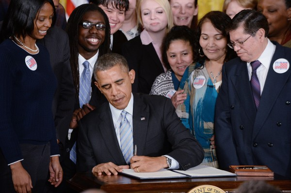 President Barack Obama signs an executive order requiring federal contractors to pay their federally funded employees on new contracts a fair wage of at least $10.10 an hour, in the East Room of the White House in Washington, D.C., on Feb. 12.