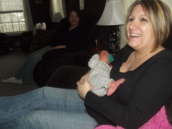 Christina Bridges laughs while holding her newborn daughter. Bridges received telephone assistance in delivering her daughter.