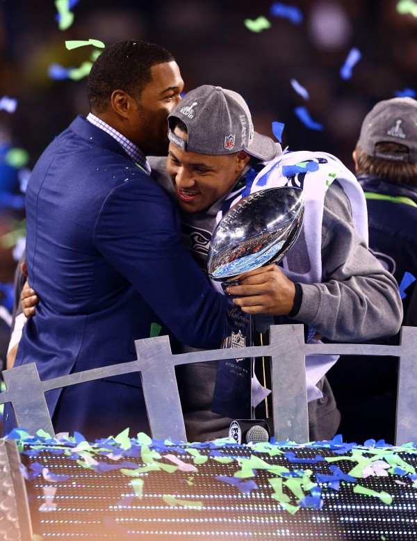 Seattle Seahawks outside linebacker Malcolm Smith hugs FOX reporter Michael Strahan (left) while holding the Vince Lombardi Trophy after Super Bowl XLVIII against the Denver Broncos at MetLife Stadium. Smith was named the game's MVP.