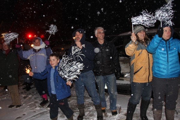 After Saturday's historic basketball tournament quarterfinal win, the North Haven Community School Hawks were met at the ferry terminal by fireworks, firetrucks and cheering community members. From left: Cheryl Beverage, in purple, Bryn Campbell and his father, Adam Campbell, Louis Carrier, Michelle Campbell and Karen Cooper held pompoms and sparklers to welcome their team home.