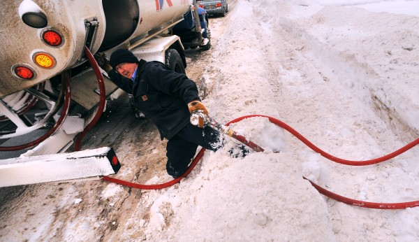 Greg Hamilton, a delivery driver with Dead River Co., struggles through a waist-high snowbank after filling the oil tank at a Brewer home in December 2013.