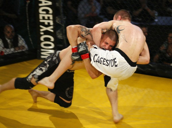 Anthony Kaponis of AFT/Galdiator, left, drives Ryan Sanders, of Youngs MMA, to the mat, during the Maine Event, Saturday, April 30, 2011, at the Stevens Avenue Armory in Portland, Maine.