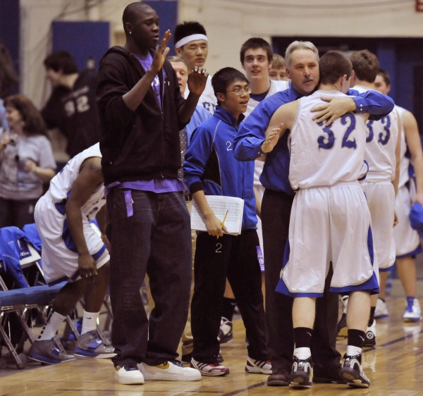 Lee Academy coach Randy Harris gives a hug to David Cropley (32) as his seniors come off the floor with the game in hand in the fourth quarter of the state Class C championship game at the Bangor Auditorium Saturday, March 5, 2011.
