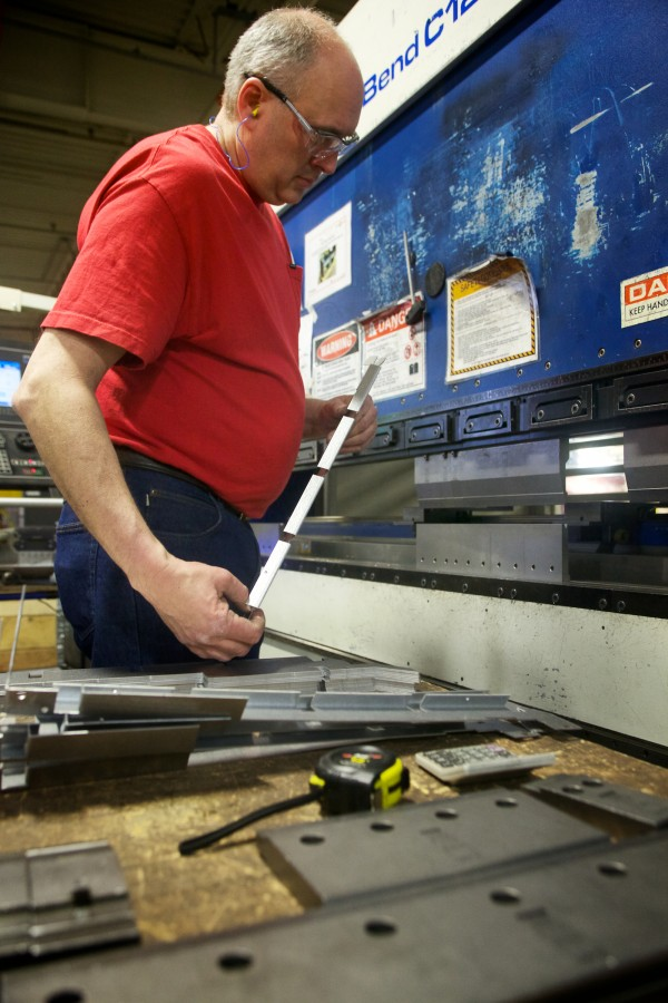 Bill Bombard uses a press brake to make sheet metal parts at Jotul North America's wood and gas stove manufacturing facility in Gorham on Friday. Proposed EPA rules would require the company to make cleaner burning, and more expensive, wood stoves.