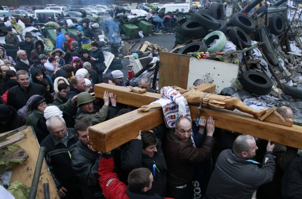 People carry a cross during a religious service at the site of the recent clashes in Kiev on Monday. Ukraine's new authorities issued an arrest warrant on Monday for mass murder against ousted President Viktor Yanukovich, who is on the run after being toppled by bloody street protests in which police snipers killed opposition demonstrators.