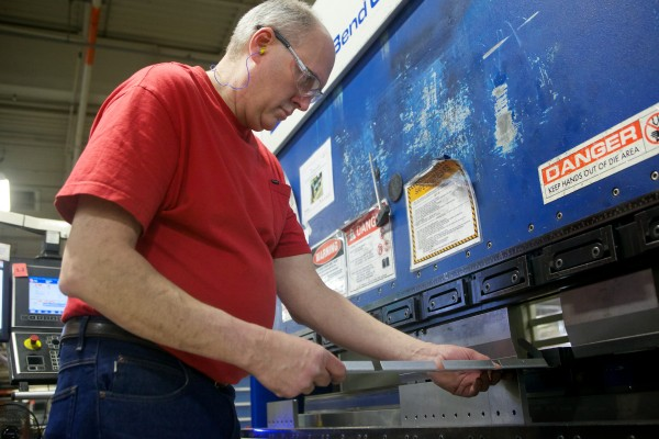 Bill Bombard uses a press brake to make sheet metal parts at Jotul North America's wood and gas stove manufacturing facility in Gorham on Friday.