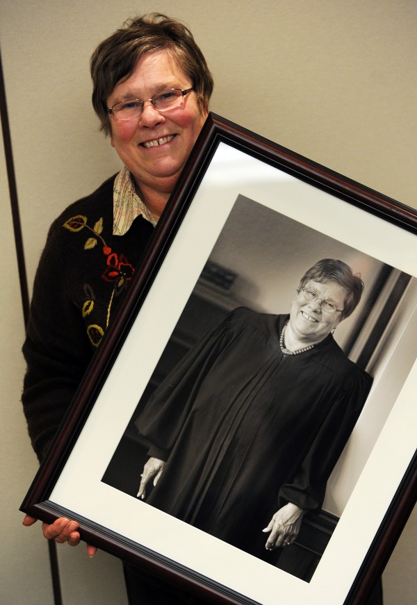 U.S. Magistrate Judge Margaret Kravchuk displays the black and white portrait of herself that will hang in the courtroom where she once presided before her retirement. Kravchuck is retiring after 25 years on the bench in state and federal court.