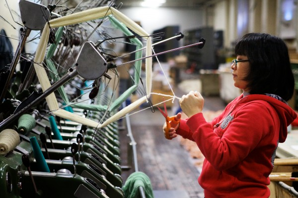 XueYan Guan winds skeined yarn onto spools at the Saco River Dyehouse in Biddeford on Tuesday. Some yarn arrives on spools, is transferred to skeins for dyeing and then put back onto spools to be shipped out.