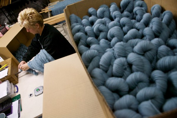 Linda Roberts twists skeins of yarn at the Saco River Dyehouse in Biddeford on Tuesday. Twisting holds the skeins together.