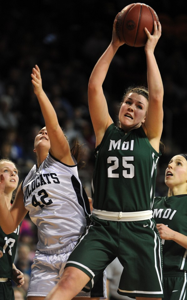 Mount Desert Island's Hannah Shaw (center) pulls a rebound away from Presque Isle's Krystal Kingsbury during the East Class B final on Feb. 22, at the Cross Insurance Center in Bangor.