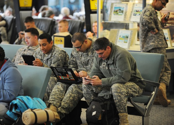 Members of the military sit and wait to board their flight at Bangor International Airport on Monday.