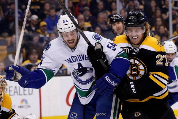 Boston Bruins defenseman Dougie Hamilton (27) battles with Vancouver Canucks left wing Kellan Lain (54) during the first period of Tuesday night's game at TD Banknorth Garden.