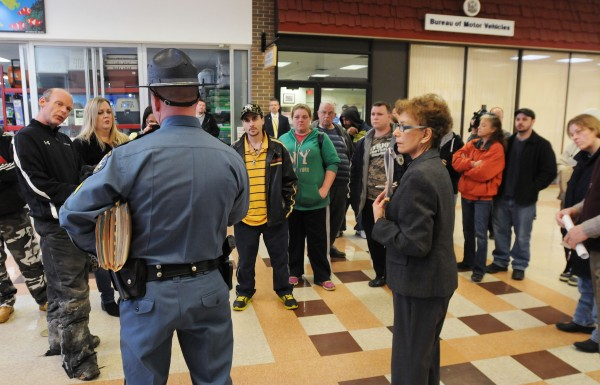 Maine State Police Trooper Bruce Scott (left) and Joanne Baumrind, hearings officer for the secretary of state, answer questions on Monday outside the Bureau of Motor Vehicles at the Airport Mall in Bangor to explain why a public hearing was not held for Glenn Geiser Jr. in regard to suspending his license to operate the My Maine Ride used car dealership in Bangor.