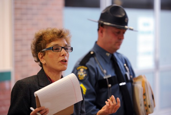 Maine State Police Trooper Bruce Scott (right) and Joanne Baumrind, hearings officer for the secretary of state, answer questions Monday outside the Bureau of Motor Vehicles at the Airport Mall in Bangor to explain why a public hearing was not held for Glenn Geiser Jr. in regard to suspending his license to operate the My Maine Ride used car dealership in Bangor.