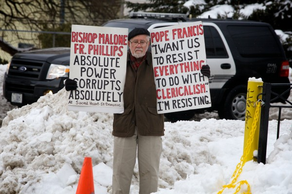 Retired University of Maine professor and congressional candidate Bill Slavick stands outside the Cathedral of the Immaculate Conception in Portland on Friday, the lone protester at the Installation Mass for new Bishop Robert Peter Deeley.