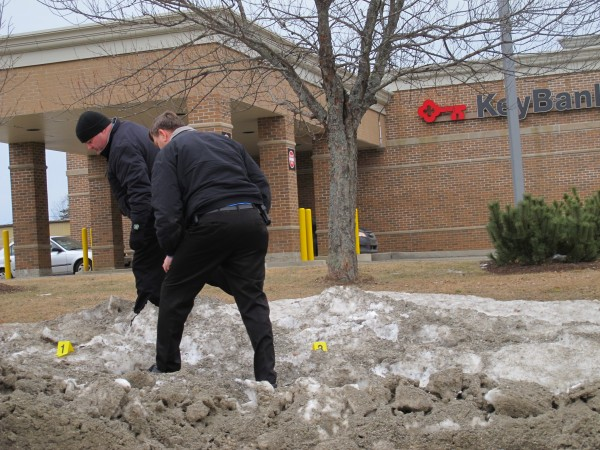 Detectives Alan Brown of the Hancock County Sheriff's Department and Steve McFarland of the Hancock County District Attorney's Office on Monday afternoon examine footprints marked by placards in a snowbank by L.L. Bean in Ellsworth. Police believe a bank robber may have run to the parking lot around 1:45 p.m. Monday after robbing Key Bank, seen in the background.