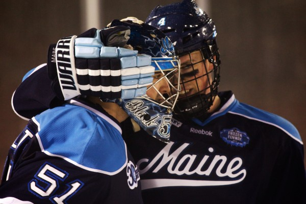 University of Maine's Jake Rutt (right) hugs goaltender Martin Ouellette after beating Boston University at Frozen Fenway in Boston on Jan. 11, 2014.