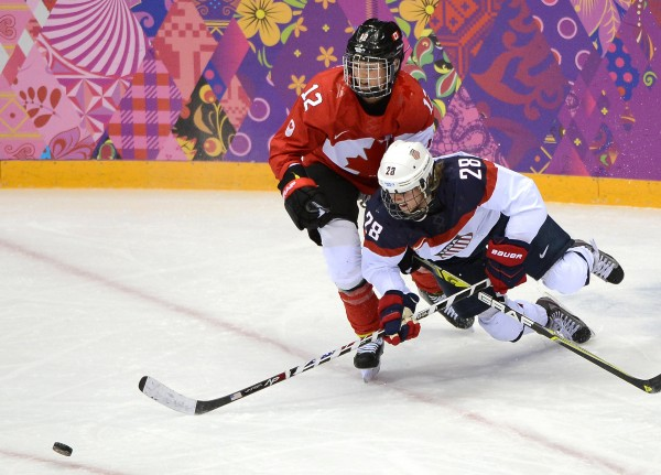 USA forward Amanda Kessel (right) goes down to the ice as she battles after the puck against Canada defenseman Meaghan Mikkelson in the third period of the women's hockey gold medal game during the Winter Olympics in Sochi, Russia, on Thursday. Canada defeated the USA in overtime, 3-2.