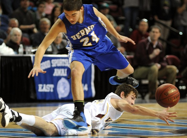 Hermon's Tyler Beaton jumps over Caribou's Matthew Milliard as they both scramble for a loose ball in the first half of a Class B semifinal game Wednesday at the Cross Insurance Center.  Caribou won the game.