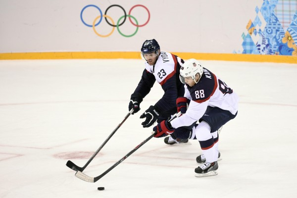 USA forward Patrick Kane (right) carries the puck past Slovakia defenseman Rene Vydareny in a men's ice hockey preliminary round game during the Sochi 2014 Olympic Winter Games at Shayba Arena on Thursday.