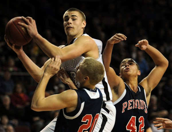 Houlton's Kyle Bouchard pulls down a rebound while surounded by Penquis's Trevor Lyford, center, and Giavani Sibert during Class C action on Friday at the Cross Insurance Center.