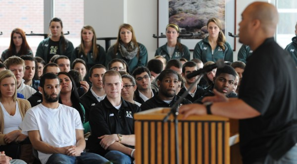 Husson football player Stevens Laguerre speaks to a packed room of Husson athletes, students and faculty at the G. Pierce Webber Campus Center at Husson University on Friday during a service of remembrance for Husson football player Stephen Colvin.
