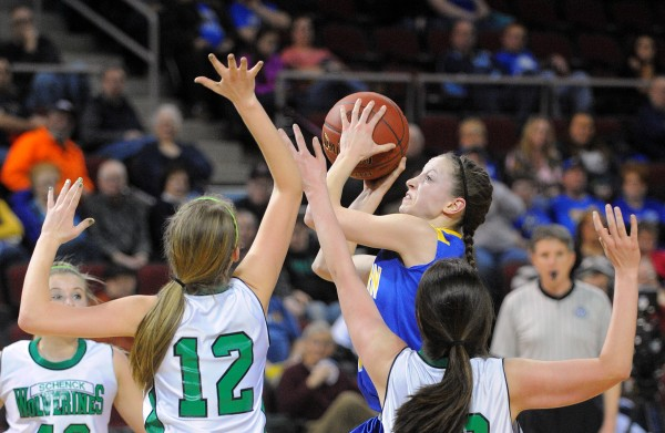 Washburn High School's Carsyn Koch (center) drives to the basket past Schenck High School's Morgan Thompson (left) and Lexie Hoxie during a Class D girls semifinal game at the Cross Insurance Center in Bangor on Thursday.
