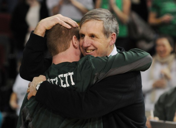 Old Town boys basketball coach Brian McDormand get s hug from center Zach Bartlett after Old Town defeated Poland 64-39 for the Class B state championship on Friday night at the Cross Insurance Center in Bangor.