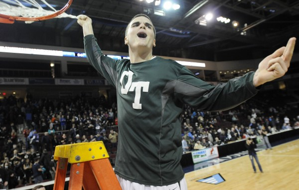 Old Town's Nicholas Cowan celebrates the Old Town Coyotes win over Poland as he takes down a net at the Class B boys state championship game on Friday night at the Cross Insurance Center in Bangor. Old Town won 64-39.