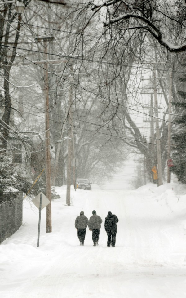 With sidewalks not yet shoveled or plowed, pedestrians take to walking in the streets around Bangor.