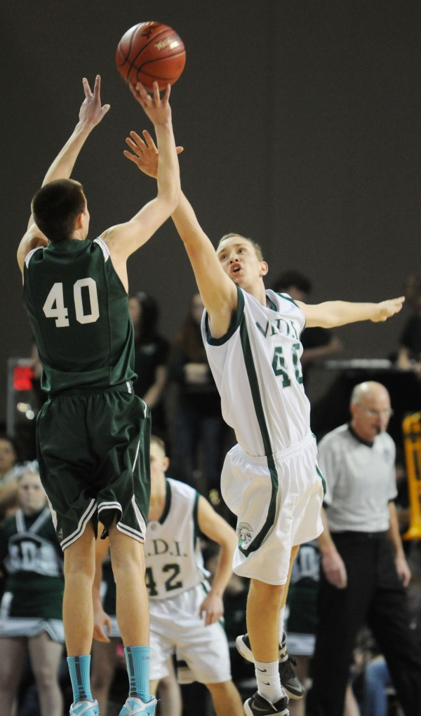 Old Town's Mitchell Cole throws up a shot with pressure from MDI's Riley Swanson on Friday night.
