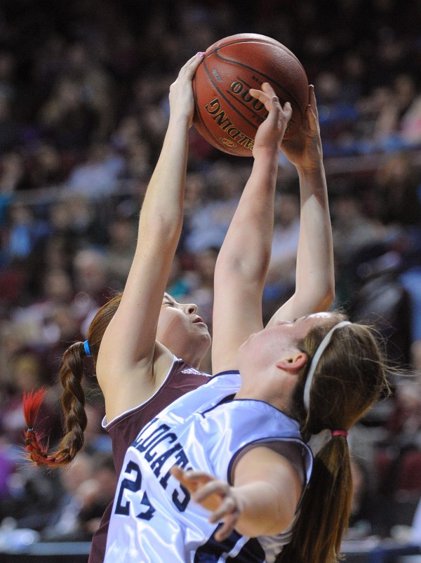 Foxcroft Academy's Brittany Dyer (left) takes a rebound over Presque Isle High School's Taylor Williams during the Class B girls semifinal game at the Cross Insurance Center in Bangor on Wednesday evening.