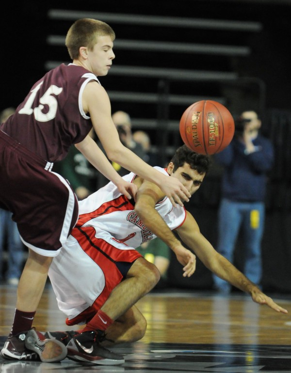 Bangor, Maine --02/14/2014-- Ellsworth's Bryce Harmon trips up Camden Hills' Yani Stancioff while trying to steal the ball on Friday night at the Cross Insurance Center in Bangor.