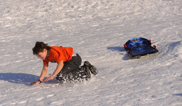 Eleven-year-old Whitfield Steele takes a spill while sledding at the Brewer Auditorium on Thursday afternoon. Whitfield and his sister, 6-year-old Ada Sinclar-Steele, both took several runs in their T-shirts in the mild weather. The temperature in the region reached the mid-40s.