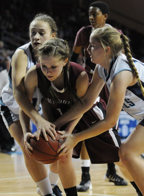 Calais's Jordan Hatch (left) and Mallory Black (right) both get their hands on a rebound brought down by Washington Academy's Whitney Porter (center) on Tuesday at the Cross Insurance Center during Class C action.