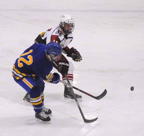 Falmouth High School's Andre Clement (left) and Bangor High School's Justin Courtney battle for the puck during their game Monday night at Sawyer Arena in Bangor.