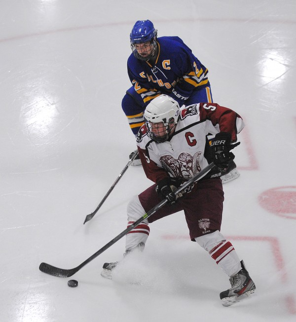 Bangor High School's Cam Dickson (bottom) and Falmouth High School's Andre Clement battle for the puck during their game at Sawyer Arena in Bangor Monday night.