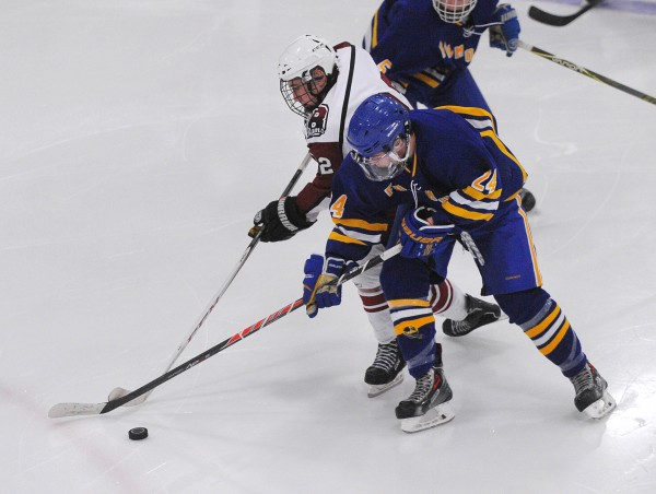 Bangor High School's Jake Fournier (left) and Falmouth High School's Jake Grade battle for the puck during their game at Sawyer Arena in Bangor Monday night.