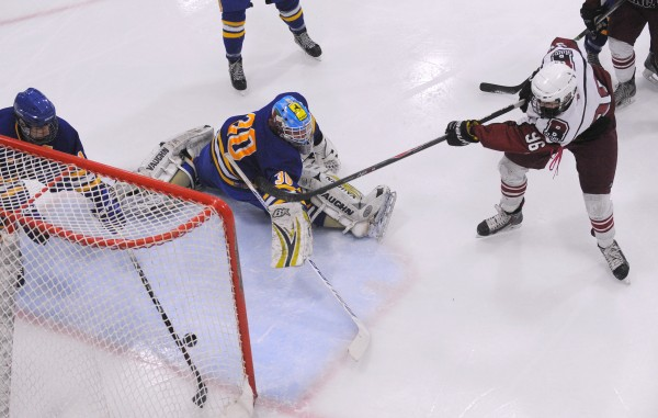 Falmouth High School goalie Brandon Boehm cannot make the save on a shot by Bangor High School's Jordan Tracy (right) during their game at Sawyer Arena in Bangor Monday night. On the left is Falmouth's Andre Clement.