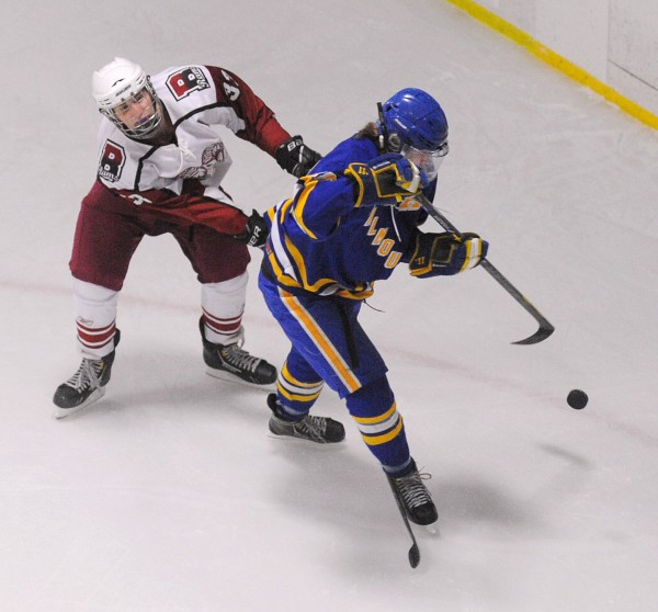 Bangor High School's Sam Kenney (left) and Falmouth High School's Isaac Nordstrom battle for the puck during their game at Sawyer Arena in Bangor Monday night.