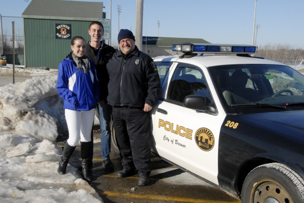 Brewer Police Officer Peter Rancourt stands beside his cruiser with Brewer High School seniors Morgan Forrest and Sam Johnson. Both Brewer residents, they are enrolled in the American Law and Trial Class taught by Andrea Jordan. Rancourt introduces class students to law enforcement; each student accompanies Rancourt on the Ride Along Program, during which a student spends about an hour with Rancourt as he patrols Brewer in his cruiser.