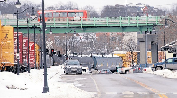 Inbound from Brewer, a BAT bus crosses the Joshua Chamberlain Bridge into Bangor as a Pan Am Railways train rumbles northbound beneath the bridge on Feb. 10.