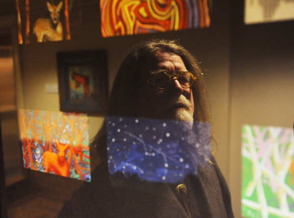 Artist Mathew Pierce O'Donnell is seen reflected in one of his pieces titled &quotBeyond Nature&quot as it hangs in the children's area of the Bangor Public Library on Monday. Pierce O'Donnell's art work will remain on display through the end of 2014.