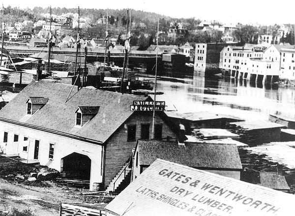 A bridge spans the St. Croix River between Calais (foreground) and St. Stephen, New Brunswick in this early 20th-century photograph. The wood-framed buildings and piled lumber along the Calais waterfront would have been similar to the city encountered by Confederate soldiers who arrived in Calais on July 18, 1864 to rob a local bank and burn the city.