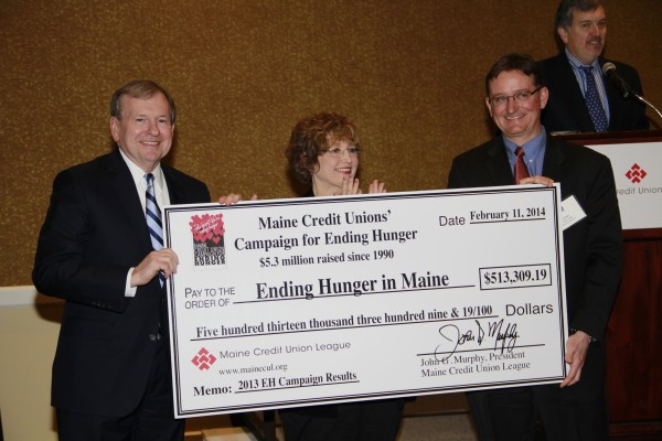 John Murphy, President of the Maine Credit Union League, Miss Sue Mitchell, the real-life tutor who tutored NFL Star Michael Oher, subject of the award-winning film The Blind Side, and Luke Labbe, Chair of the Maine Credit Union League's Social Responsibility Committee, proudly hold up the check displaying the record-setting amount raised by Maine's credit unions through the Maine Credit Unions' Campaign for Ending Hunger in 2013.