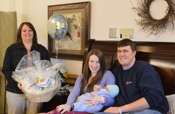 Crystal Cummings (left), ACAP community education specialist for oral health, presents a special gift basket full of dental education materials and products to Alan Brown and Anarae Holmes of Mapleton who had the first baby born in February at TAMC.  February is National Children's Dental Health Month.  ACAP presents the gift basket as a way to kick off the special month and raise awareness about the importance of dental health in children.  Items in the basket will be given to newborn Alex Douglas Brown when he is older.