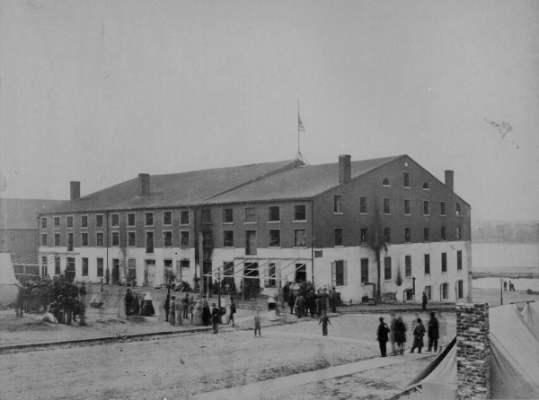"The American flag flies above the infamous Libby Prison in Richmond, Va. after Union troops captured that city in early April 1865. Forming an entire city block, the three brick buildings were purchased in 1861 by Maine merchant Luther Libby. He hung outside his warehouse a sign that read ""Libby and Son, Ship Chandlers and Grocers.&quot The warehouse soon became a prison for Union officers captured during the Civil War."