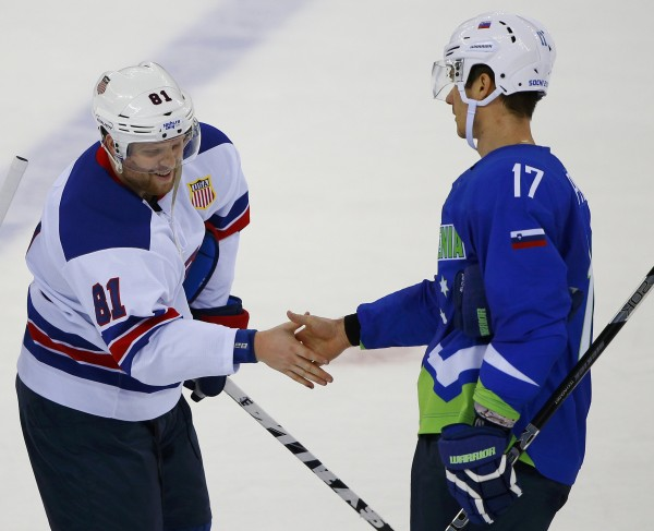 Team USA's Phil Kessel (left) shakes hands with Slovenia's Ziga Pavlin after Team USA defeated Slovenia in the men's preliminary round ice hockey game at the 2014 Sochi Winter Olympics, February 16, 2014.